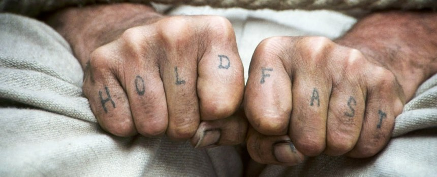 """Two fists held close together. On each knuckle a letter is tattooed. The words """"Hold Fast"""" are spelled out across them."""
