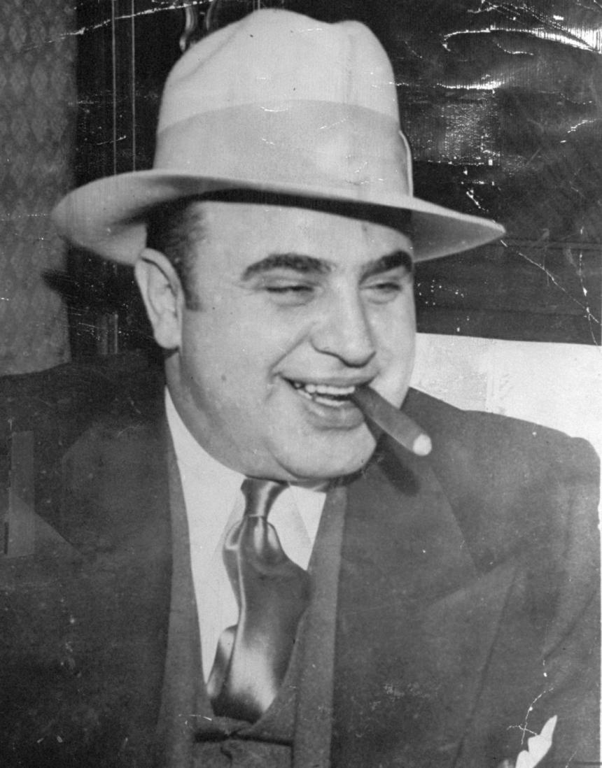 Al Capone smiling with a cigar in his mouth